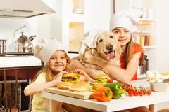 在厨师的帽子吃汉堡包的两只女孩和宠物 免版税库存照片