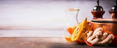 在厨房书桌桌上的南瓜与烹调罐、油和姜,正面图 烹调启发的秋天的食物背景 库存图片