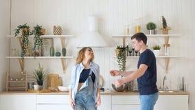 在厨房佩带的牛仔裤的愉快的年轻夫妇跳舞跳舞 影视素材