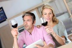 在厨房品尝酒的夫妇 免版税图库摄影
