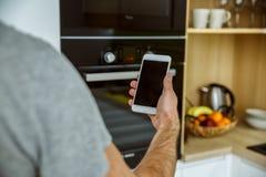 在厨房唯一生活方式概念的学士人每日惯例与智能手机特写镜头 库存图片