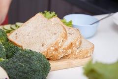 在厨房屋子里切面包,为做准备做三明治 库存图片