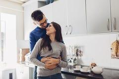 在厨房拥抱的和饮用的茶的年轻夫妇 免版税库存图片