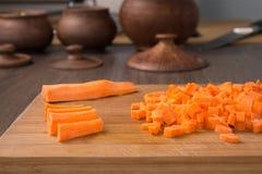在厨房板的切成小方块的红萝卜 库存图片