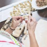 在厨房用桌上放置装填、立即可食的饺子和面团 免版税图库摄影