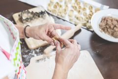 在厨房用桌上放置装填、立即可食的饺子和面团 库存图片