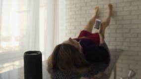 在厨房用桌上的一个黑无线报告人身分 在在同一张桌上的背景中的美女与 股票录像