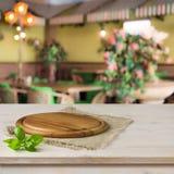 在厨房用桌上的圆的委员会在咖啡馆内部背景 图库摄影