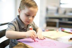在厨房用桌上的年轻男孩图画 免版税库存图片
