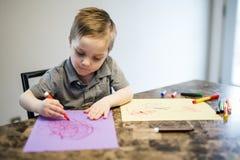 在厨房用桌上的年轻男孩图画 库存图片