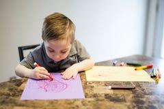 在厨房用桌上的年轻男孩图画 库存照片
