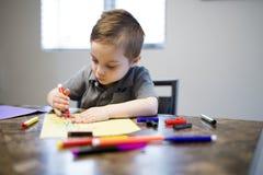 在厨房用桌上的年轻男孩图画 免版税库存照片