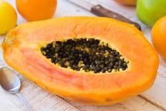 在厨房用桌上的成熟水多的被对分的番木瓜用柑橘水果和苹果,在板条木头桌上的刀子 免版税库存图片