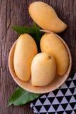 在厨房用桌上的新鲜的黄色芒果 免版税图库摄影