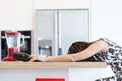 在厨房用桌上的醉酒的妇女 免版税库存图片