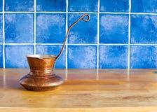 在厨房用桌上的铜咖啡壶 免版税库存图片