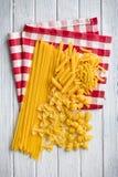 在厨房用桌的多种原始的意大利面食 免版税图库摄影
