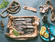在厨房用桌背景的未加工的沙丁鱼与成份 柠檬、大蒜和草本鲜美海鲜烹调的 免版税图库摄影