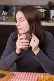 在厨房的女孩饮用的茶 库存图片