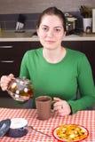 在厨房的女孩饮用的茶 库存照片