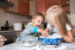 在厨房的孩子烹调晚餐的和获得乐趣 免版税库存图片