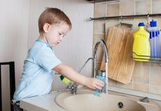 在厨房的孩子男孩洗涤的盘 免版税库存图片