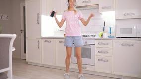 在厨房的无忧无虑的妇女跳舞在听到在耳机的音乐的早晨 影视素材