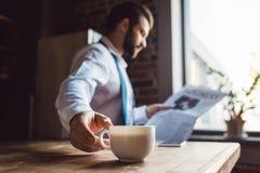 在厨房的被集中的商人读书报纸在早晨,当有杯子时 免版税库存图片