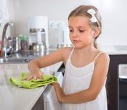 在厨房的逗人喜爱的小女孩清洁 免版税库存照片