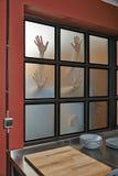 在厨房窗口的可怕手 库存图片