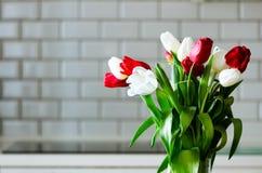 在厨房背景的新鲜的白色和红色郁金香 从丈夫,人的礼物 Copyspace 免版税库存图片