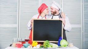 在厨房里享受乐趣展开 主要厨师和拥抱在烹饪学院的预习功课厨师 在人爱的夫妇和 免版税库存图片