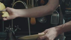 在厨房里供以人员在家洗盘子的` s手 股票视频
