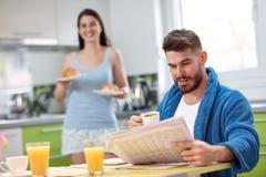 在厨房里供以人员读报纸并且吃新月形面包 免版税库存图片