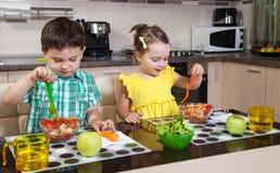 在厨房里吃健康食物的两个学龄前孩子 免版税库存图片