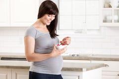 在厨房里吃快餐的孕妇 库存图片