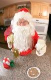 在厨房里吃曲奇饼的圣诞老人 库存图片