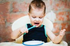 在厨房里吃细面条用牛奶的孩子 免版税库存图片