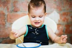 在厨房里吃细面条用牛奶的孩子 图库摄影