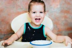 在厨房里吃细面条用牛奶的孩子 库存图片