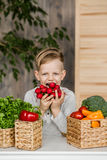 在厨房里吃菜的英俊的小男孩 素食主义者 健康的食物 图库摄影
