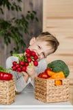 在厨房里吃菜的英俊的小男孩 素食主义者 健康的食物 库存图片