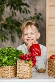 在厨房里吃菜的英俊的小男孩 素食主义者 健康的食物 免版税图库摄影