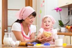 在厨房里哄骗有做面团的妈妈的女孩 免版税库存图片