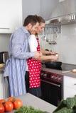 在厨房里烹调一起油煎的年轻新已婚夫妇 免版税库存图片