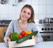 在厨房里烹调与新鲜蔬菜的可爱的妇女 库存图片