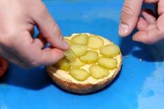 在厨房里烹调加在汉堡的黄瓜 免版税库存图片