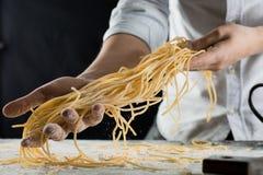 在厨房里烹调拿着新近地煮熟的意粉 免版税图库摄影