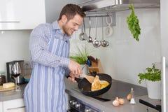 在厨房里烹调煎蛋的年轻人 图库摄影