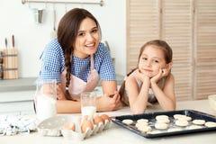 在厨房里照顾和她的女儿用曲奇饼面团 图库摄影